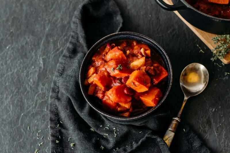 Veganer Kürbis-Bohnen-Eintopf in schwarzem Teller vor dunklem Hintergrund.