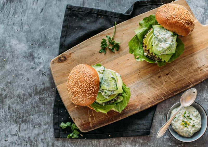 Frisch zubereiteter veganer Burger mit Mangold von oben fotografiert auf einem Holzbrett.