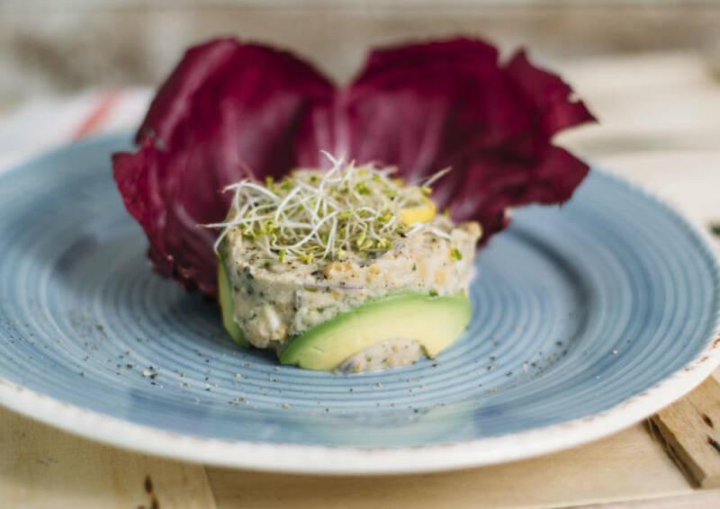 Veganer Thunfischsalat mit Nori-Algen-Flocken, liebevoll auf einem blauen Teller angerichtet.