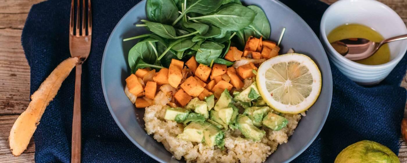 Gesunde Bowl mit Hirse, Süßkartoffel-Würfeln, Avocado und Spinat. Dazu gibt es leckeres Zitronendressing, von oben fotografiert.