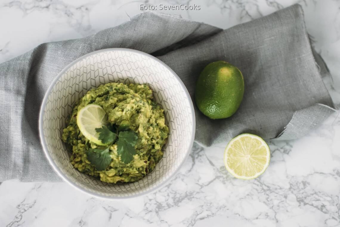 Veganes Rezept: Guacamole mit aufgeschnittener Limette in Schüssel angerichtet