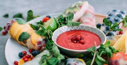 Süße Summerrolls gefüllt mit Obst und Früchten der Saison auf einem Teller. In der Mitte ein pinker Himbeer-Minze-Dip. von der Seite fotografiert.