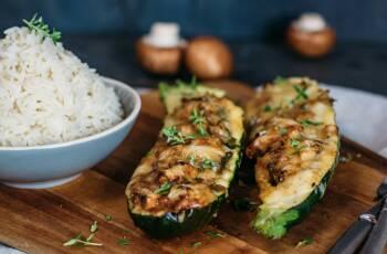 Zwei Zucchini Hälften gefüllt mit Pilzen und Zwiebeln und mit Käse überbacken, daneben Reis in einer Schüssel.