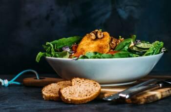 Panierter Schafskäse auf Salatbett in einer Schüssel, auf einem Holzbrett, daneben liegen zwei Scheiben Brot und Besteck.