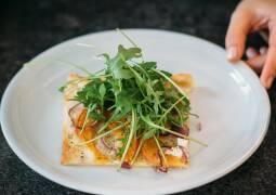 Vegetarisches Rezept: Kürbis-Flammkuchen mit Rucola-Haube