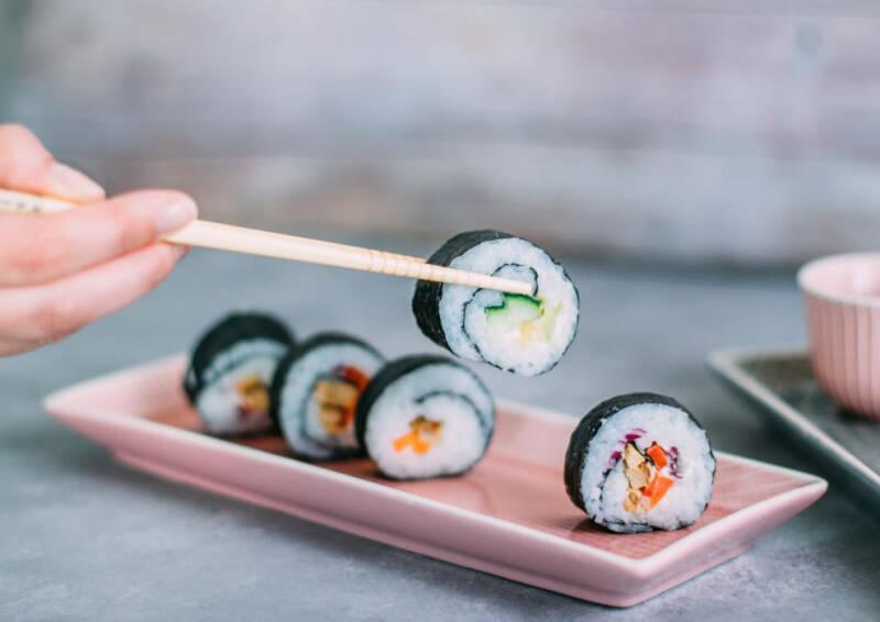 Frisch gerolltes Sushi wird mit Stäbchen vom Teller angehoben.