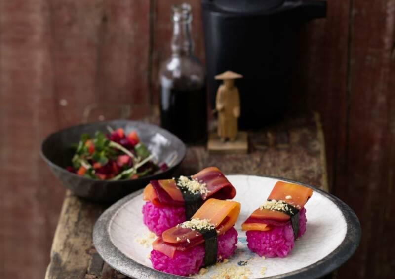 Veggie-Nigiri mit pinken Reis auf einem Teller, von vorne fotografiert.