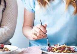 Nudeln mit Walnuss-Majoran Pesto. Eine Frau sticht mit der Gabel in die Nudeln auf dem Teller