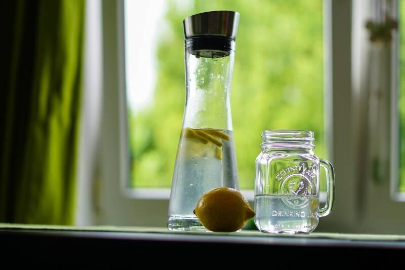 Viel Wasser zu trinken ist beim gesunden Abnehmen sehr wichtig. Hier sieht man eine Karaffe mit Wasser und Zitronenscheiben gefüllt, daneben ein halb gefülltes Glas.