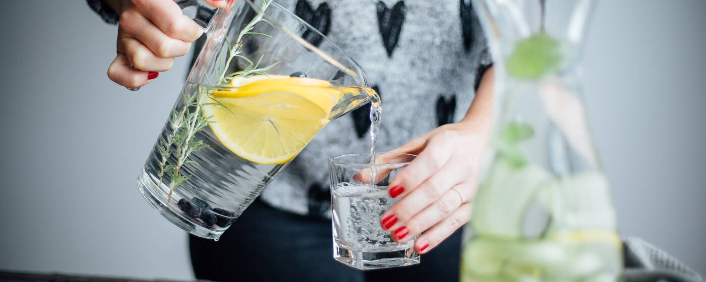 Frau schenkt Infused Water aus einem Krug in ein Glas
