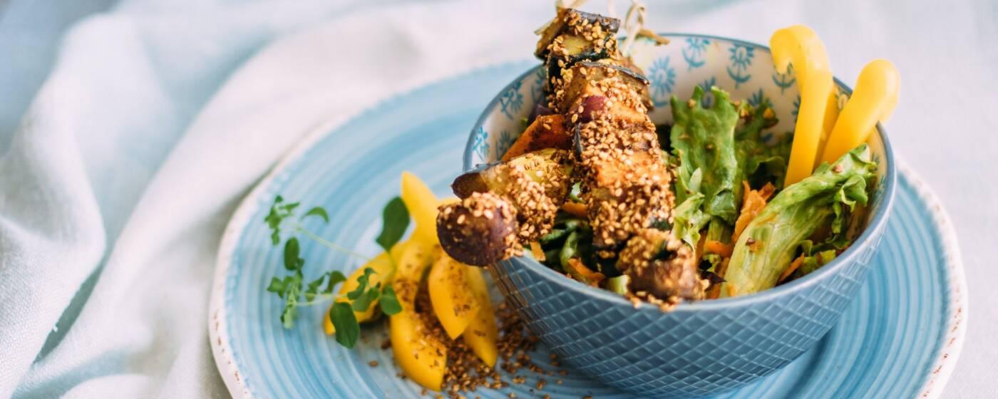 Kulinarische Inspirationen direkt aus Indien. Wie zum Beispiel diese leckeren Masala-Spieße im Gomasiomantel. In einer Schale, garniert mit Salat und Paprika, von oben fotografiert.