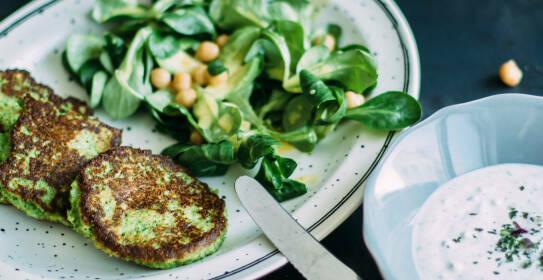 7 Gerichte, die gute Laune machen. Wie diese Brokkoli-Parmesan-Bratlinge mit Feldsalat auf einem Teller. Daneben ein Kräuter-Dip. Von oben fotografiert.