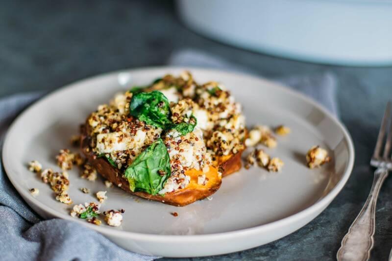 Ofensüßkartoffel mit Quinoa, Feta und Spinat auf einem Teller von der Seite fotografiert.