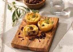 Käsemuffins auf Holzbrett mit Kirchen und Oliven