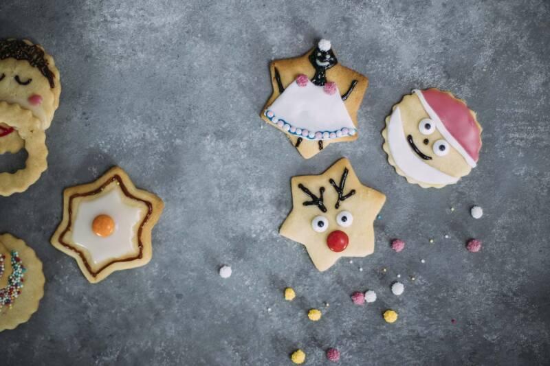 Butterplätzchen mit buntem Zuckerguss und Perlen dekoriert: Stern, Nikolaus, Engel. Von oben fotografiert.