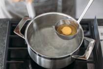 Topf mit kochendem Wasser, Schöpflöffel mit aufgeschlagenem Ei für pochierte Eier