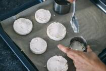 Mandeltrestermasse wird mit Hilfe von einem Servierring auf Backblech mit Backpapier zu runden Stücken geformt.