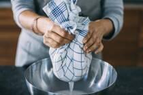 Geschirrtuch mit Mandelmilch darin wird mit den Händen zusammengefasst und ausgepresst, sodass Flüssigkeit aus Tuch in Schüssel läuft.