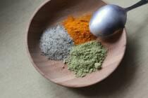Holzteller und Löffel mit Matcha, Kurkuma und Salz