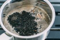 Schwarzen losen Tee in Topf mit Wasser und Gewürzen geben