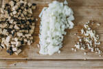 Zubereitung: Zwieblen, Knoblauch und Räuchertofu in Würfeln auf Holzbrett