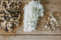 Zwieblen, Knoblauch und Räuchertofu in Würfeln auf Holzbrett