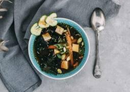 Misosuppe mit Frühlingszwiebeln und Karotten in blauer Schale, Löffel und grauem Tuch