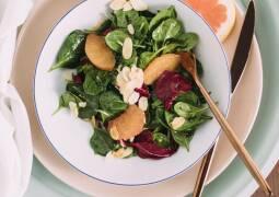 Babyspinat-Salat mit Grapefruitfilets servierfertig auf Teller mit Besteck