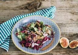 Salat mit Feigendressing auf Teller angerichtet. Auf Holztisch stehend mit Serviette und aufgeschnittener Feige daneben.